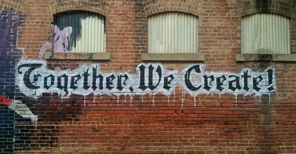 together we create graffiti on red brick wall